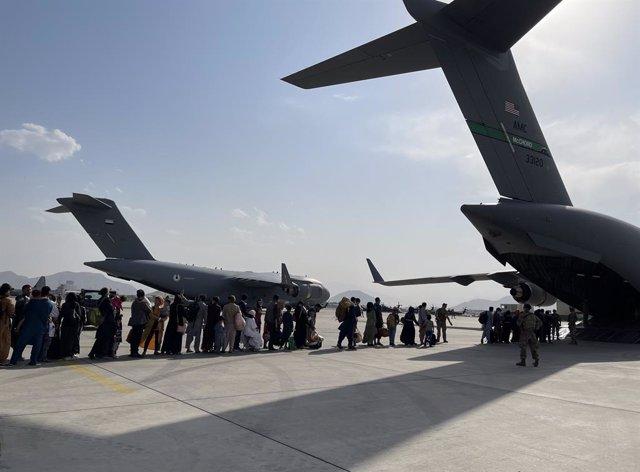 La gente hace cola para subir a uno de los aviones de evacuación en el aeropuerto de Kabul