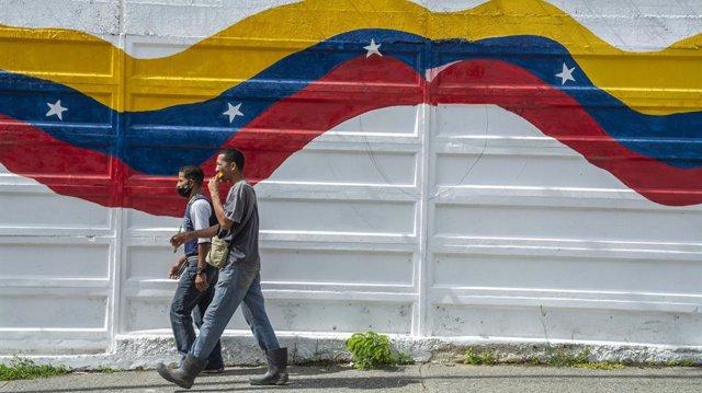 Archivo - Dos personas pasan ante un mural con la bandera de Venezuela en Caracas
