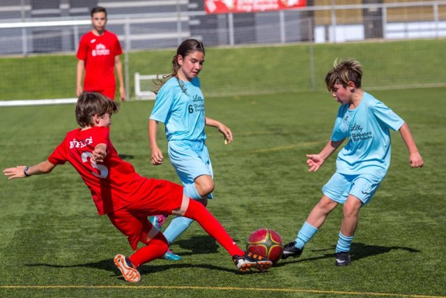 Archivo - Niños jugando al fútbol