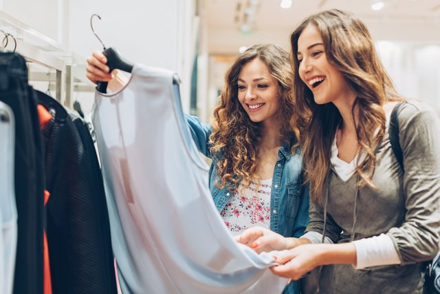 Dos chicas en una tienda mirando ropa