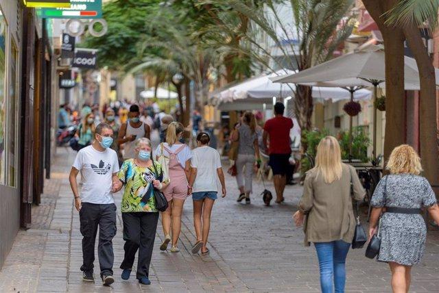 Archivo - Gente con mascarilla paseando por la calle