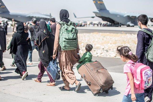 Un grupo de personas se dirigen a un avión durante una evacuación en el aeropuerto de Kabul