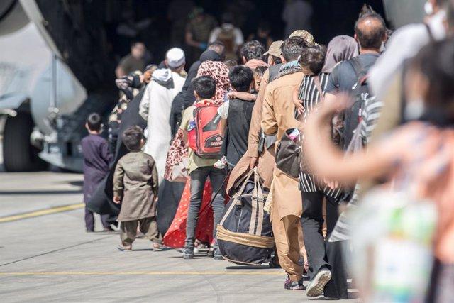 HANDOUT - 24 August 2021, Afghanistan, Kabul: Afghan evacuees board a a US Air Force C-17 Globemaster III aircraft, during evacuation at Hamid Karzai International Airport following the Taliban takeover. Photo: Sgt. Samuel Ruiz/U.S. Marine/Planet Pix via