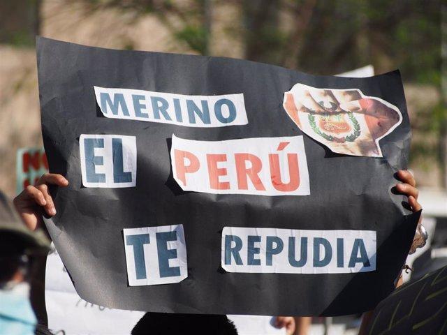 """Archivo - Un participante en las protestas contra el expresidente Manuel Merino sostiene una pancarta que reza """"Merino, el Perú te repudia""""."""