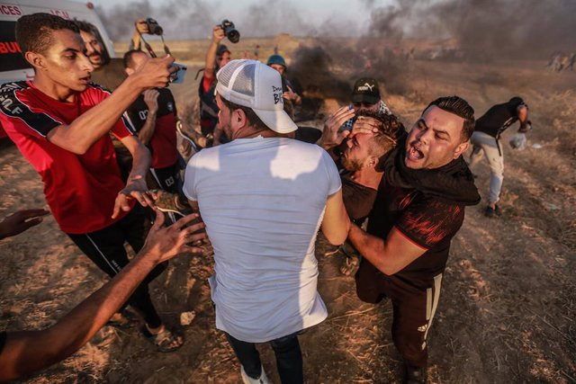 25 August 2021, Palestinian Territories, Khan Yunis: Palestinian demonstrators carry an injured man during a protest along the border fence, east of Khan Yunis in the southern Gaza Strip denouncing the Israeli blockade of the Palestinian sector. Photo: Mo