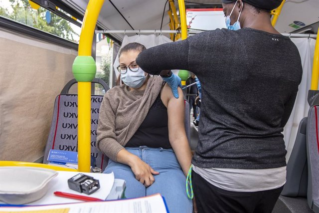 20 August 2021, North Rhine-Westphalia, Boenen: A woman receives a coronavirus vaccine at a vaccination bus in the courtyard of the Boenen community centre. Photo: David Inderlied/dpa