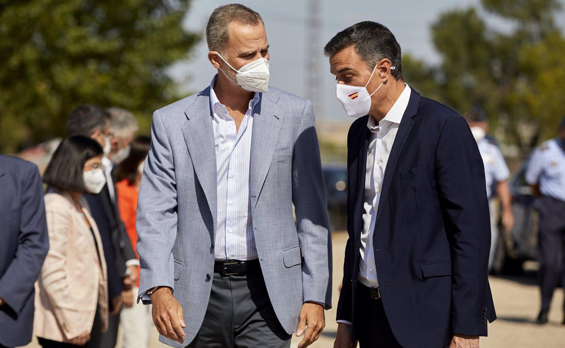 El Rey Felipe VI (i) y el presidente del Gobierno, Pedro Sánchez, conversan a su llegada al Pabellón de Cuadros de Mando de la Base Aérea de Torrejón donde han acudido para visitar el dispositivo provisional en Torrejón de Ardoz