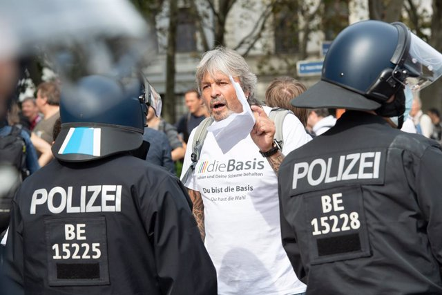 28 August 2021, Berlin: Policemen argue with a man during a protest against coronavirus-related policies. Photo: Paul Zinken/dpa