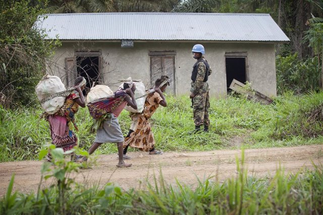 Archivo - Un 'casco azul' de la MONUSCO junto a unas mujeres en Beni, en el este de RDC