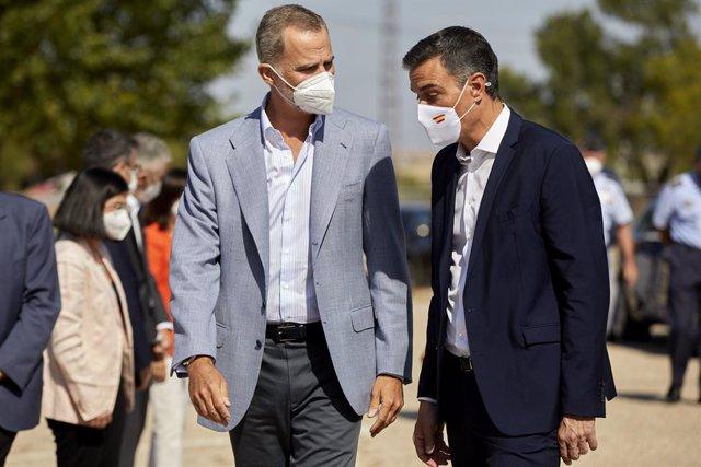 El Rey Felipe VI (i) y el presidente del Gobierno, Pedro Sánchez, conversan a su llegada al Pabellón de Cuadros de Mando de la Base Aérea de Torrejón donde han acudido para visitar el dispositivo provisional en Torrejón de Ardoz, a 28 de agosto de 2021, e