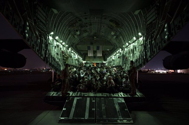 HANDOUT - 21 August 2021, Afghanistan, Kabul: Soldiers from the United States Air Force 816th Expeditionary Airlift Squadron stand next to Afghan passengers being evacuated from Kabul aboard a Boeing C-17 following the Taliban takeover. Photo: U.S. Air Fo