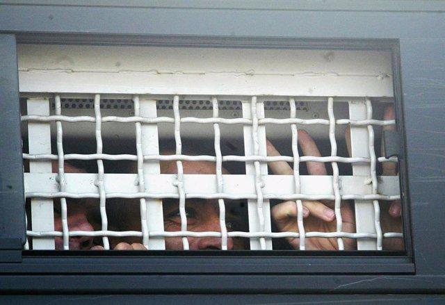 Un preso hace una señal de victoria en un furgo durante un traslado desde una cárcel israelí