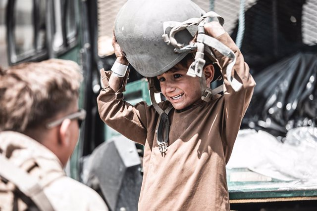 HANDOUT - 22 August 2021, Afghanistan, Kabul: A US marine soldier plays with a young child at the Hamid Karzai International Airport during the evacuation of civilians following the Taliban takeover. Photo: -/U.S. Marines via ZUMA Press Wire Service/dpa -