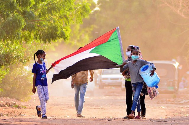 Archivo - 30 June 2020, Sudan, Khartoum: Children hold the Sudanese national flag as they talk part in an anti-government protest despite a tight curfew since April designed to curb the spread of the novel coronavirus. Photo: Faiz Abu Bakr/APA Images via