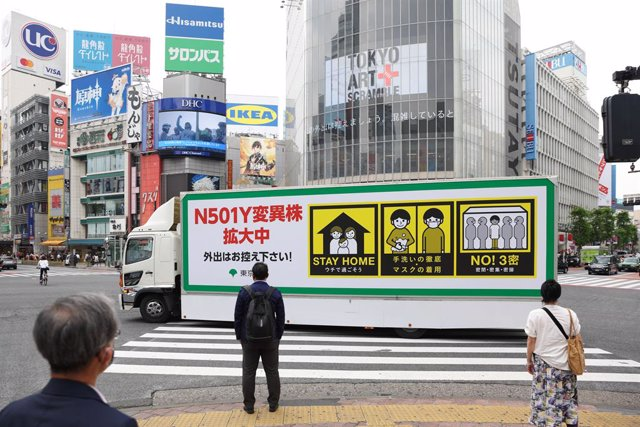 """Archivo - 24 May 2021, Japan, Tokyo: A truck with the note """"N501Y Coronavirus variation is spreading, please refrain from going outside!"""" drives around Shibuya Station in Tokyo. Four of these trucks organized by the Tokyo City Government to inform the pub"""