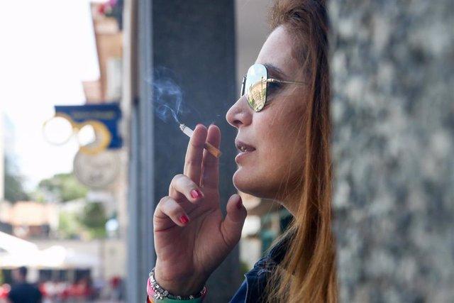 Archivo - Mujer fumando un cigarro.