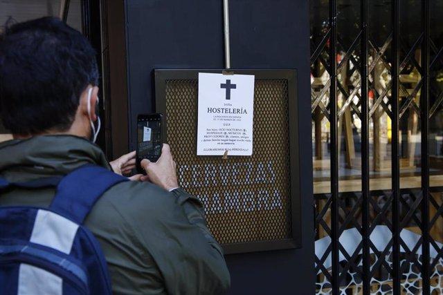 Archivo - Un joven fotografía una esquela puesta en un bar  de una de las calles comerciales de la ciudad de Granada, vacía y con sus comercios y bares cerrados, a 10 de noviembre 2020