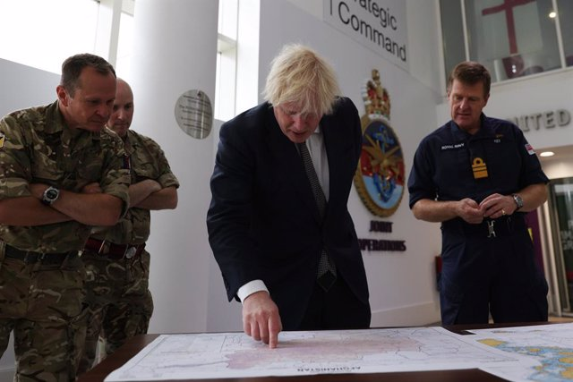 26 August 2021, United Kingdom, London: UK Prime Minister Boris Johnson observes the operations room for the Afghan Relocation and Assistance Policy during a visit to the Northwood Headquarters, the British Armed Forces Permanent Joint Headquarters, where