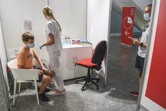 Una sanitaria vacuna a un adolescente con la primera dosis de la vacuna Moderna
