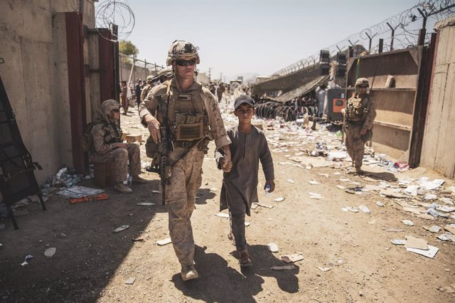 HANDOUT - 24 August 2021, Afghanistan, Kabul: A US marine escorts an Afghan child to his family during an evacuation at Hamid Karzai International Airport following the Taliban takeover. Photo: Ssgt. Victor Mancilla/U.S. Marin/Planet Pix via ZUMA Press Wi