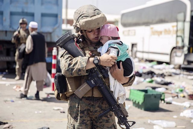 28 August 2021, Afghanistan, Kabul: Asoldier of the Special Purpose Marine Air-Ground Task Force Crisis Response team, calms an infant waiting for evacuation at Hamid Karzai International Airport during Operation Allies Refuge in Kabul. Photo: Ssgt. Vict