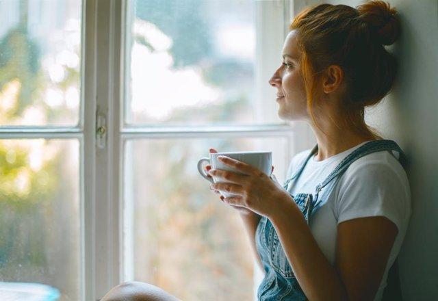 Mujer tomando una taza de café junto a la ventana,