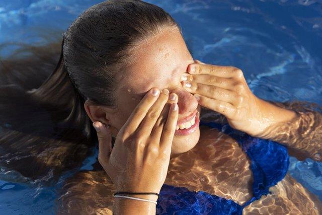Archivo - Niña frotándose los ojos en la piscina.