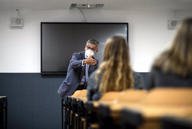 Archivo - Un profesor da clase con mascarilla en la Facultad de Humanidades y Ciencia de la Comunicación de la Universidad privada CEU San Pablo durante el primer día del curso 2020-2021, en Madrid (España), a 14 de septiembre. Desde el pasado 7 de septie