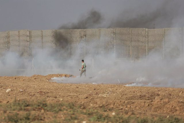 21 August 2021, Palestinian Territories, Gaza: A Palestinian protester runs away as tear gas canisters shot by Israeli security forces from across the Gaza border fall following a demonstration, denouncing the Israeli siege of the Palestinian strip. Photo