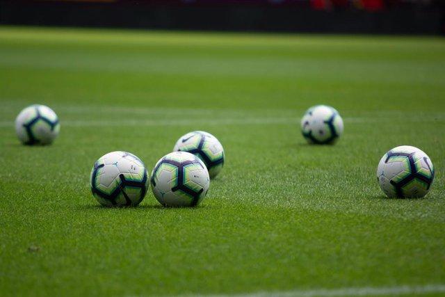 Archivo - Pelotas en un campo de fútbol