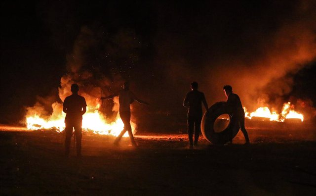 30 August 2021, Palestinian Territories, Gaza City: Palestinian protesters burn tyres during a demonstration along the border between the Gaza Strip and Israel east of Gaza City denouncing the Israeli blockade of the Palestinian sector. Photo: Ahmed Zakot