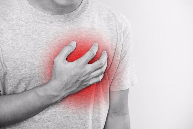 Archivo - A man touching his heart, with red highlight of heart attack,heart failure and others heart disease