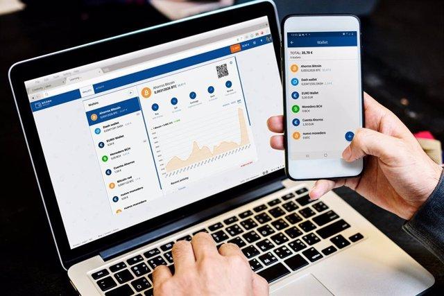 Archivo - Una persona opera en su ordenador y móvil con Bit2Me