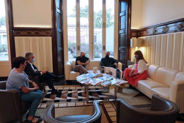 Membres d'Editors.cat donen els llibres a la presidenta del Parlament de Catalunya, Laura Borràs