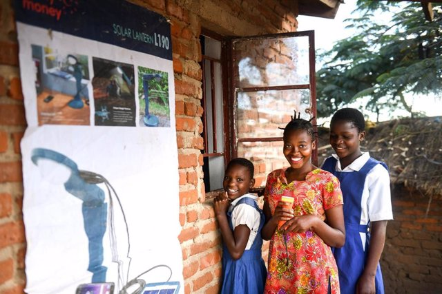 Archivo - 13-year-old Aliya Ali (right) and her friends rents a torch from Solar Money offices in Dzindebvu Village, Kasungu Central Malawi on Thursday 29 April 2021