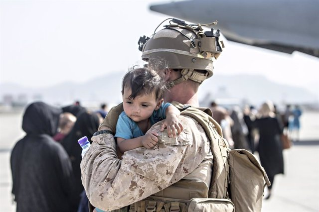HANDOUT - 22 August 2021, Afghanistan, Kabul: A US marine soldier carries a young boy at the Hamid Karzai International Airport during the evacuation of civilians following the Taliban takeover. Photo: Sgt. Samuel Ruiz/U.S. Marine/Planet Pix via ZUMA Pres