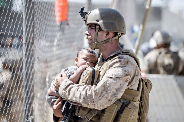 28 August 2021, Afghanistan, Kabul: Asoldier of the Special Purpose Marine Air-Ground Task Force Crisis Response team, holds an infant waiting for evacuation at Hamid Karzai International Airport during Operation Allies Refuge in Kabul. Photo: Sgt. Samue