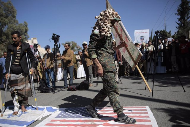 Archivo - 18 January 2021, Yemen, Sanaa: AHouthi soldier walks on a USflag during a protest in front of the USembassy in Sanaa against the United States over its decision to designate the Houthi rebels movement as a foreign terrorist organization. Phot