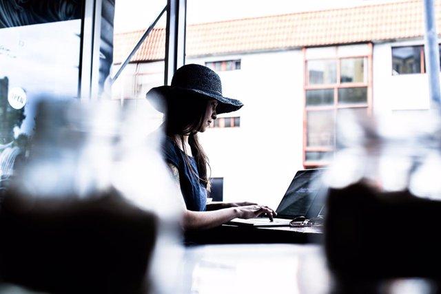 Archivo - Mujer utilizando un portátil, ciberseguridad.