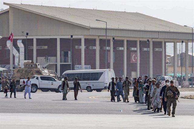 20 August 2021, Afghanistan, Kabul: A US Marine soldier leads Afghan civilians to a US Air Force C-17 Globemaster III aircraft during the evacuation process at Hamid Karzai International Airport. Photo: Sra Taylor Crul/U.S. Air/Planet Pix via ZUMA Press W