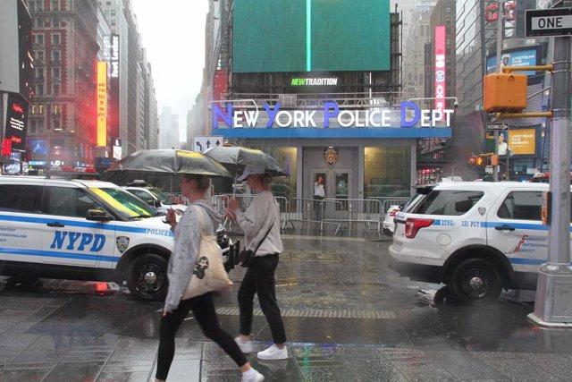 Vianants es protegeixen de la forta pluja amb paraigua mentre creuen un carrer en Estafis Square