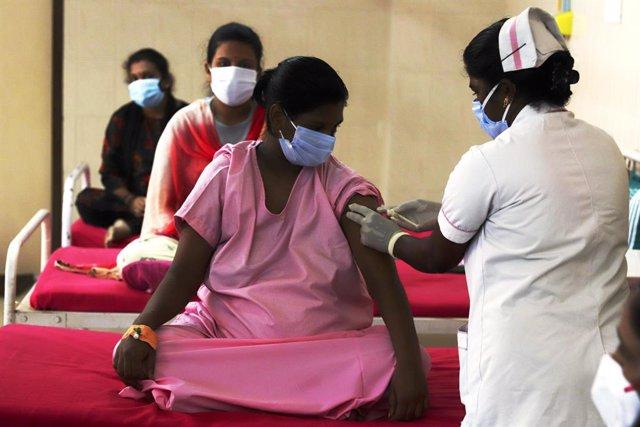 Archivo - Una mujer es vacunada contra el coronavirus en India