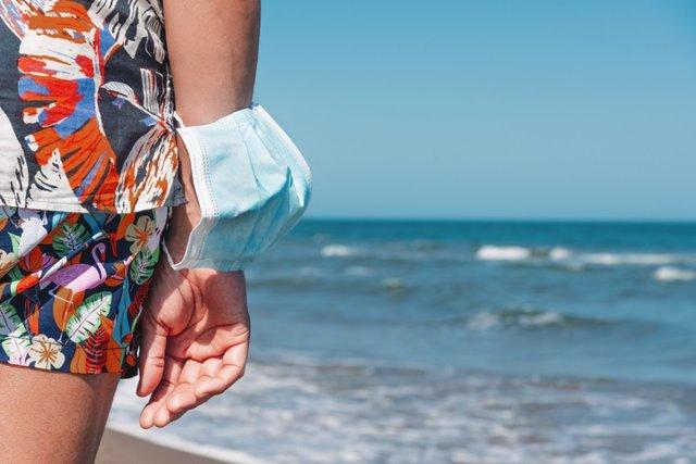 Archivo - Hombre frente al mar con la mascarilla en el brazo.