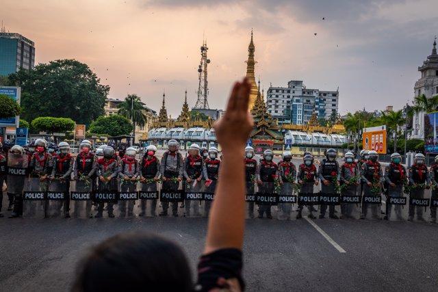 Un manifestante hace un saludo de tres dedos frente a una fila de policías antidisturbios, que sostienen rosas que les dieron los manifestantes, el 6 de febrero de 2021 en Rangún, Birmania.