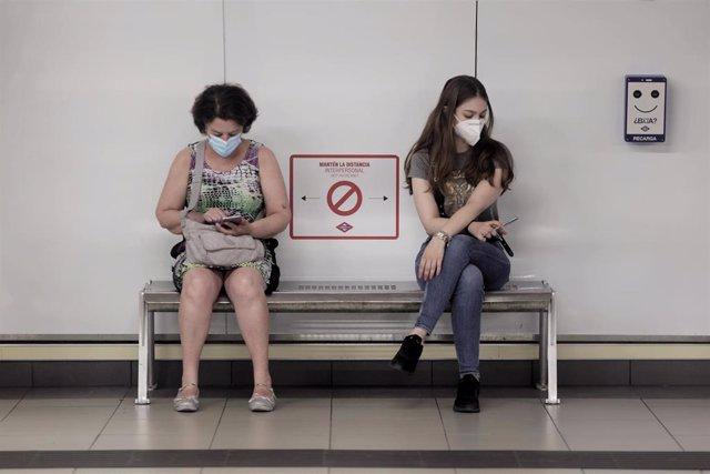 Archivo - Dos mujeres consultan el móvil sentadas, separadas con la conveniente separación por el COVID-19, en un banco de un andén de la estación de metro de Sol, a 14 de junio de 2021, en Madrid (España). CCOO, UGT y USO convocaron para hoy el inicio de