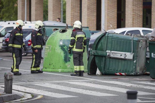 Los bomberos colocan los contenedores tirados por los manifestantes, durante el desalojo de la nave ocupada como gaztetxe (local juvenil), en el barrio de la Rochapea de Pamplona, a 2 de septiembre de 2021, en Pamplona, Navarra (España).