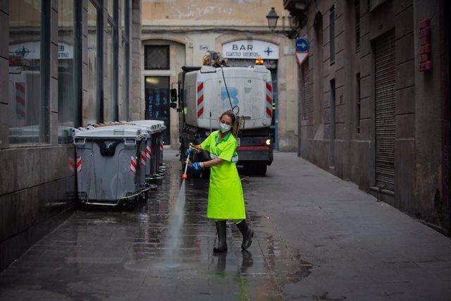 Archivo - Una trabajadora limpia una vía de Barcelona, a 26 de julio de 2021, en Barcelona, Catalunya, (España). Con motivo de la temporada estival, Barcelona refuerza con 200 personas su servicio de limpieza y mantenimiento de las zonas verdes de la ciud