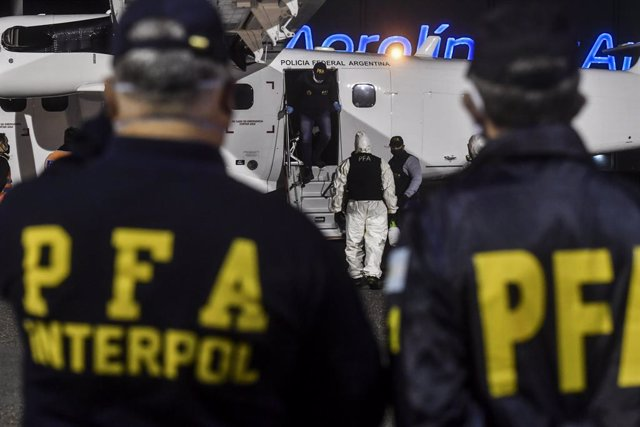 Archivo - 15 May 2020, Argentina, Buenos Aires: Interpol officials wait for the arrival of Gonzalo Sanchez, a former Argentine naval officer who is allegedly implicated in dictatorship-era crimes, at Ezeiza airport after his extradition from Brazil. Photo