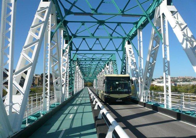Archivo - Un autobús metropolitano cruza el puente metálico de San Juan de Aznalfarache