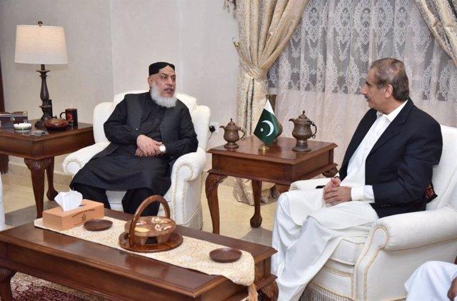 Uno de los jefes de la ofician política de los talibán, Muhamad Abbas Stanakzai, conversa con el embajador de Pakistán en Qatar, Syed Ahsan Raza Shah.